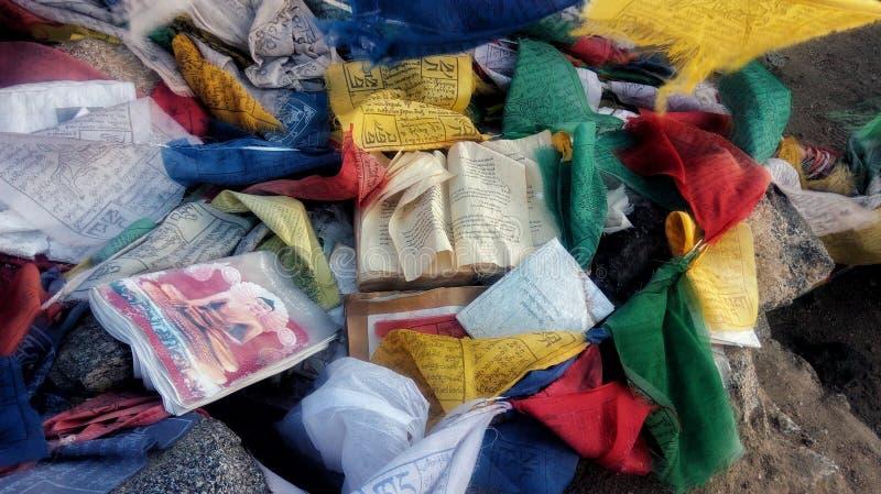 Tibetana kulöra flaggor med mantras och böcker royaltyfri foto