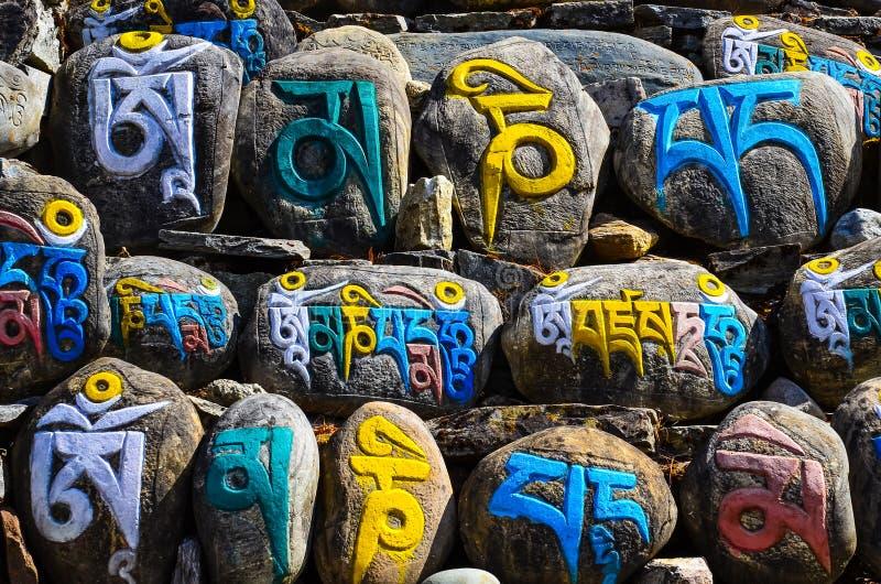 Tibetana religiösa budhistsymboler på stenar royaltyfria foton