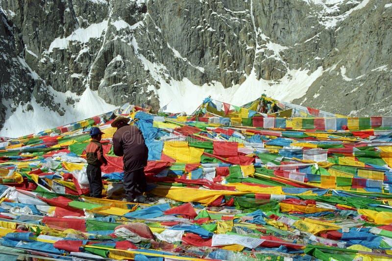 Tibetanische Pilger bringen hervor und Sohn hängen die Gebetsflaggen Lungta auf Drolma-La-Durchlauf lizenzfreie stockfotos