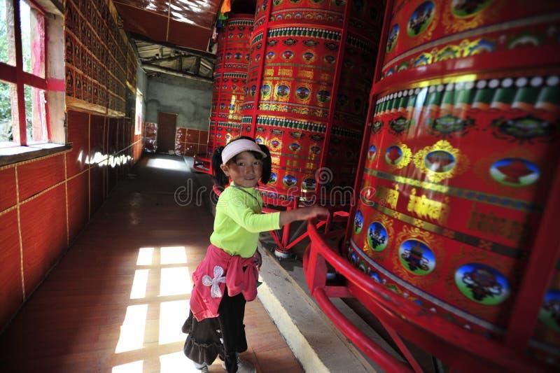 A Tibetant Kid Turning Prayer Wheels royalty free stock photo
