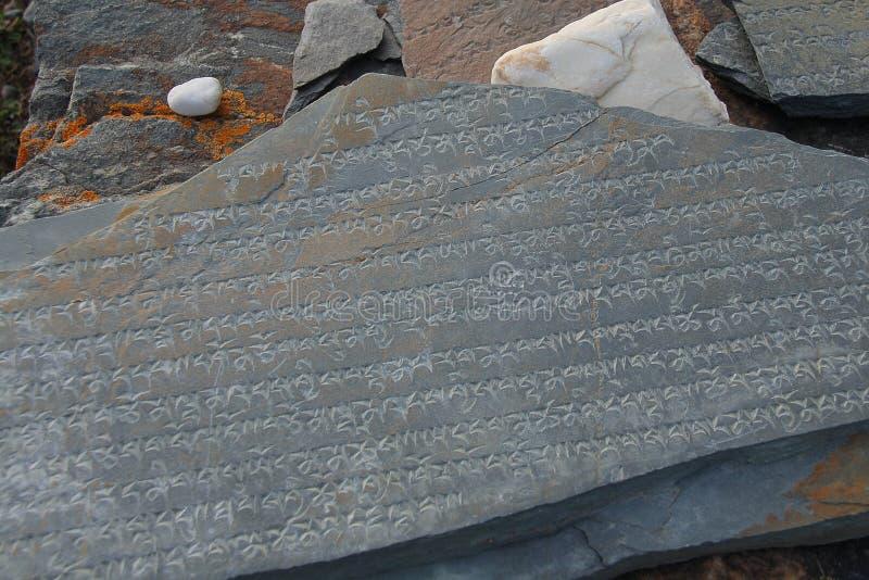 Tibetant språk som snidas på den Marnyi stenen arkivfoton