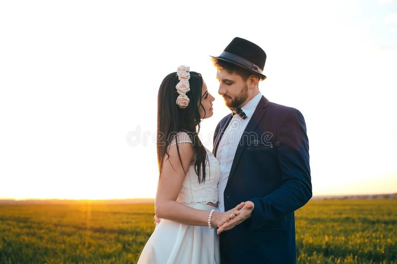 Romantic feelings in the field at sunset, the groom looks at the bride, the girl loves his boyfriend. Tic feelings in the field at sunset, the groom looks at the royalty free stock photos