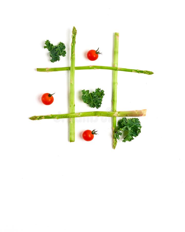 tic tac toe with food, asparagus kale, tomato, top view stock photos