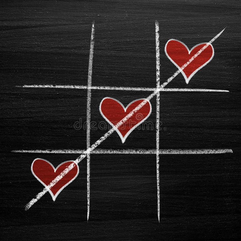 Tic tac toe game with chalk hearts, XO noughts and crosses Valentine`s Day style royalty free stock photo