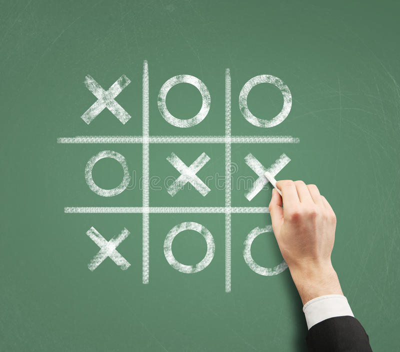 Tic tac toe. Hand playing a game of tic tac toe on a chalkboard royalty free stock images
