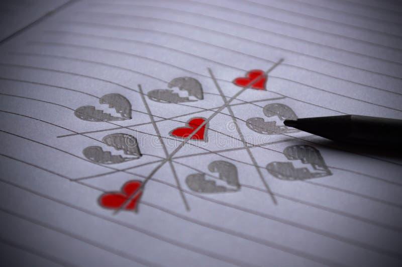 Tic-tac-toe-spel met een kruising en harten op papier royalty-vrije stock afbeelding