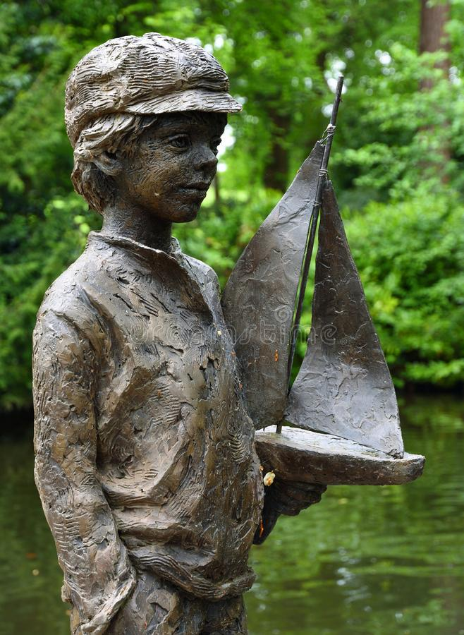 Statue of Boy with pond yacht Pashley Manor Gardens. royalty free stock photography