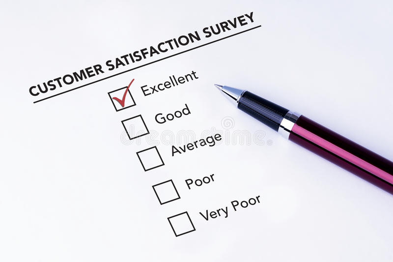 Tick placed in excellent check box on customer service satisfaction survey form with a pen on isolated white background. Business stock image