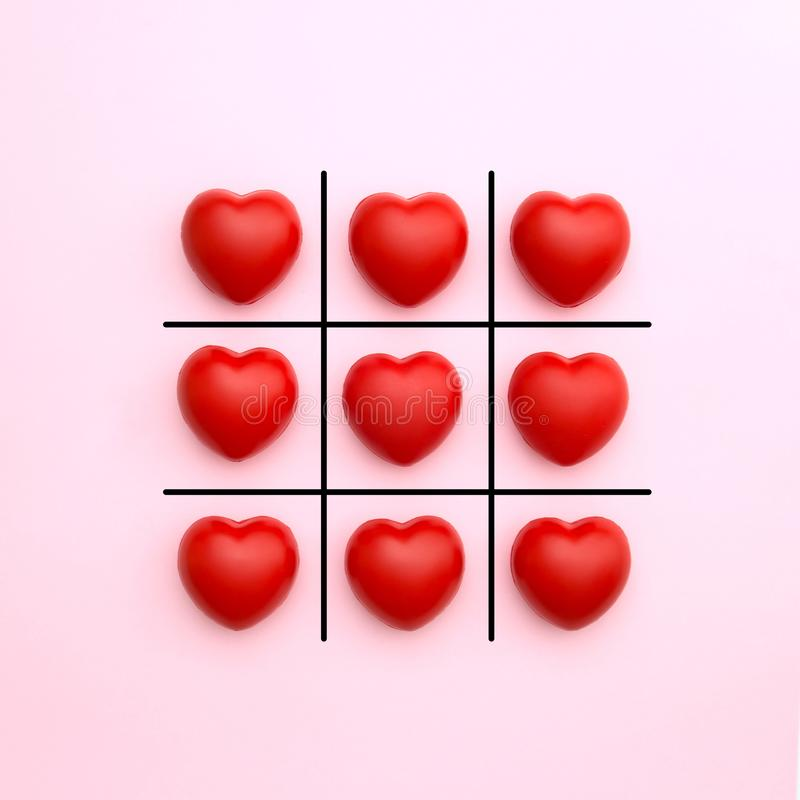 Tick tack toe made from red heart on pink background stock photos