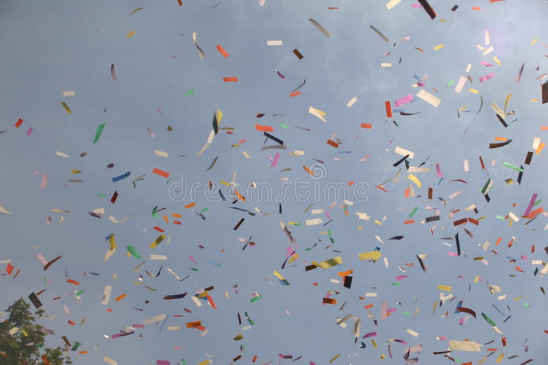 Ticker tape released at an event. Shown against a blue sky with flare from the sun in the corner stock images