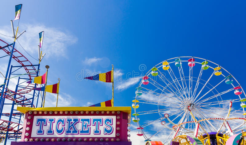 Ticket Booth and Rides at a Carnival Against Blue Sky stock images