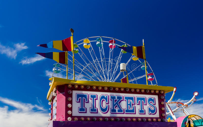 Ticket Booth and Rides at a Carnival Against Blue Sky stock photo