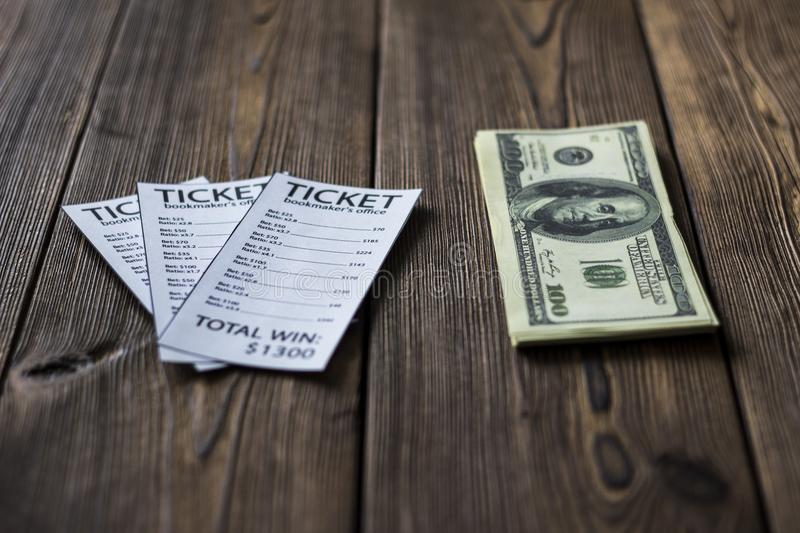 Tickets of the bookmaker office and money dollars lie on a wooden table, close-up. Sports betting stock photography