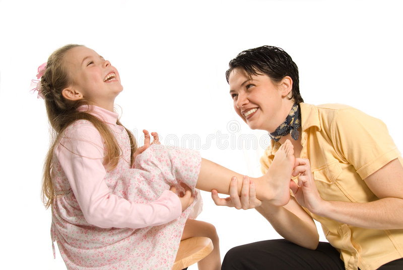 Tickle. Mom tickling daughter on white background laughing royalty free stock photos