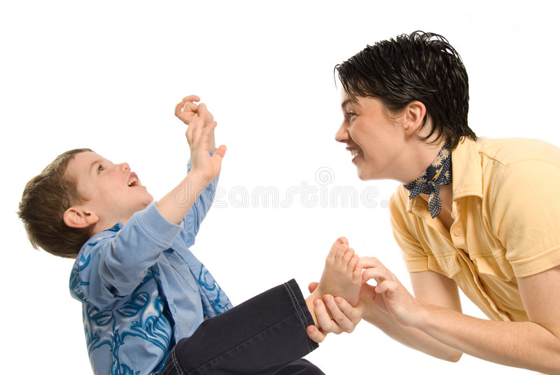 Tickle, tickle. Son being tickled by mom on white background royalty free stock images