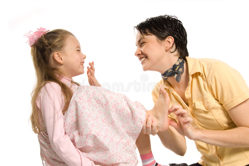 Tickling. Mom and daughter playing tickling on white background stock photo