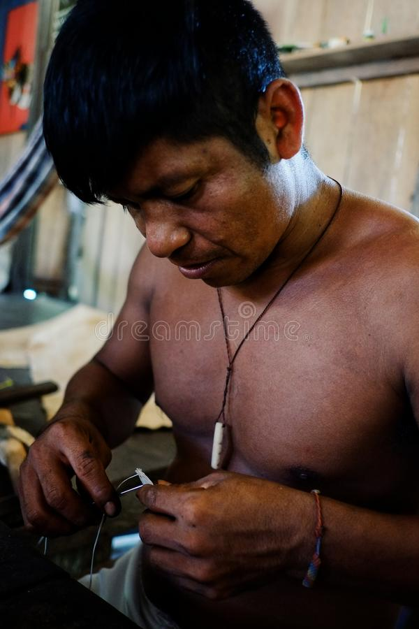 Ticuna indian tribal member stitching a tree bark artifact together stock photography