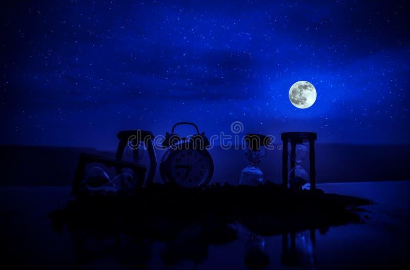 Tid begrepp med ett timglas på natten med månen eller sand som passerar till och med exponeringsglaskulorna av ett timglas som mä arkivbild