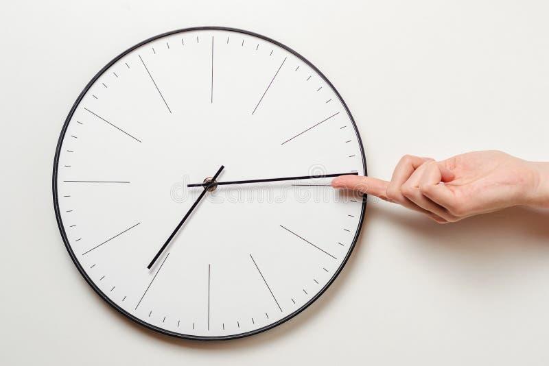Tid för kvinnahandstoppet på den runda klockan, tar det kvinnliga fingret den minimala pilen av klockan tillbaka, tidledning och  arkivbild
