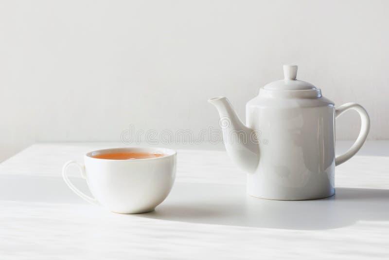 tid f?r tea f?r klockalivstid fortfarande Ställ in av koppen och tekannan på vit Minsta sammans?ttning royaltyfria foton