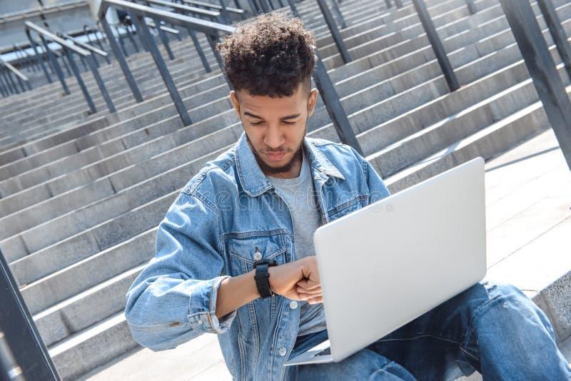 Tid ledning Mulattgrabb som sitter på trappa genom att använda bärbara datorn som kontrollerar fundersam cllose-up för tid fotografering för bildbyråer