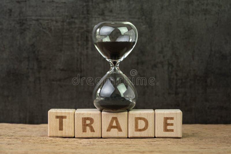 Tid nedräkning för handelkrig, växling på aktiemarknad, timglas eller sandglass på träkubkvarteret med alfabetbyggande royaltyfri bild