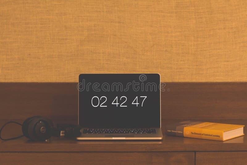 Tid på en bärbar dator med hörlurar och en bok royaltyfria foton