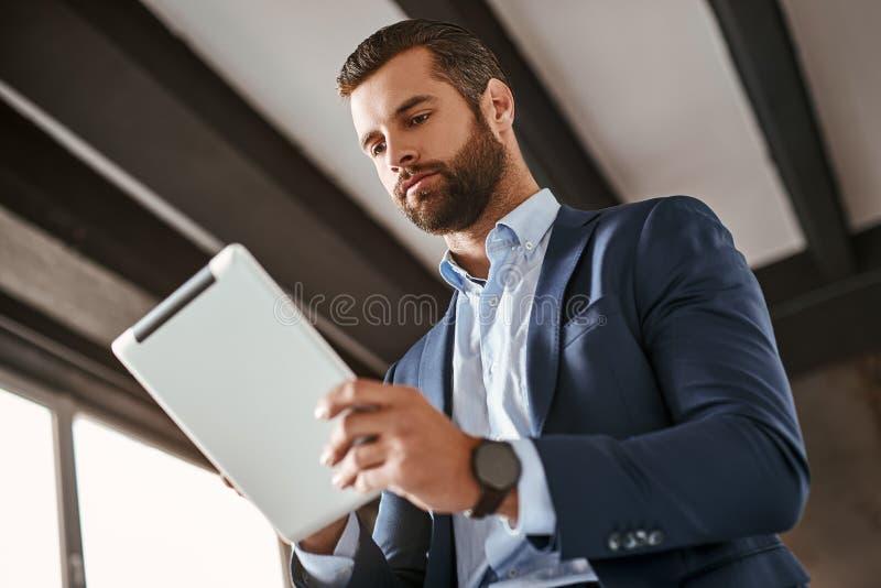 Tid som arbetar! Den säkra skäggiga unga affärsmannen i stilfull dräkt använder den digitala minnestavlan fotografering för bildbyråer