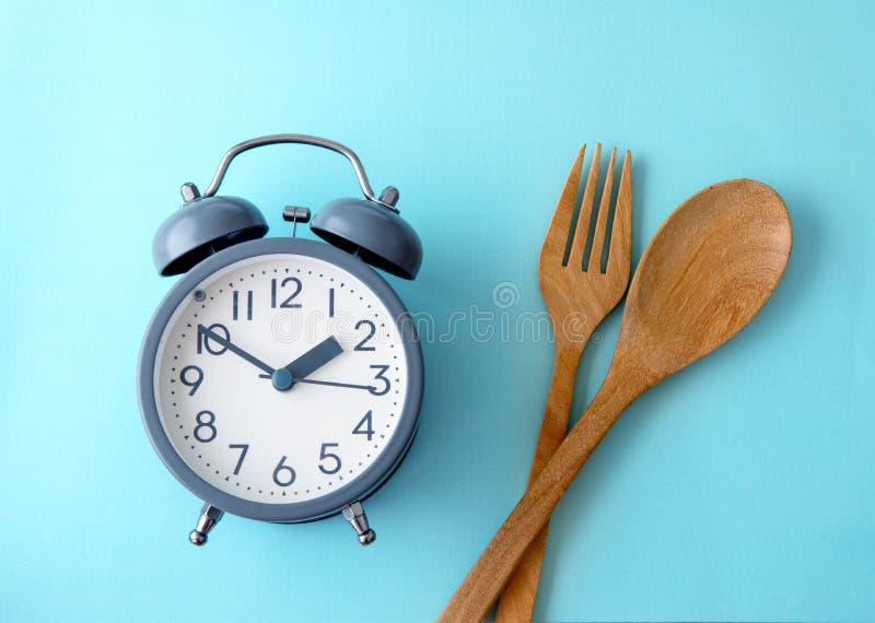 Tid som förlorar vikt och att äta kontroll eller tid för att banta begrepp, en ringklockagarnering på blå bakgrund royaltyfria foton