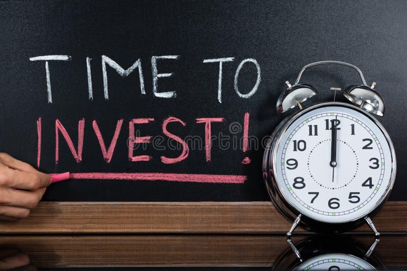 Tid som investerar begreppet som är skriftligt på svart tavla arkivbilder