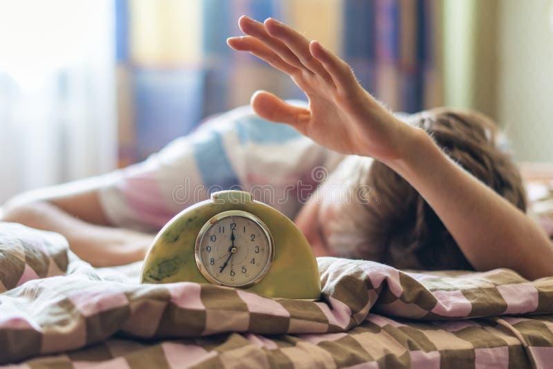 Tid som vaknar upp och att sova att ligga i sängman, slår ringklockan i morgonen f royaltyfria foton