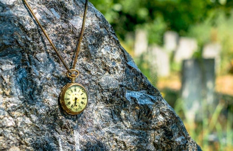 Tid som vilar den antika murkna rovan på den svarta marmorgravstenen i kyrkogården arkivbild