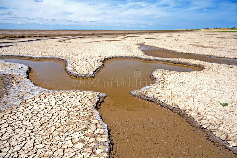 Tidal Wash Estuary Mudflats in Norfolk, England. The wide empty mudflats and channels of the Wash estuary nature reserve at low tide under a blue sky. Snettisham stock photography