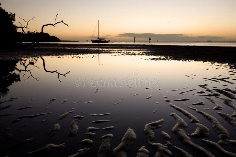 Tidal Flat and Sailboat at Sunset stock images