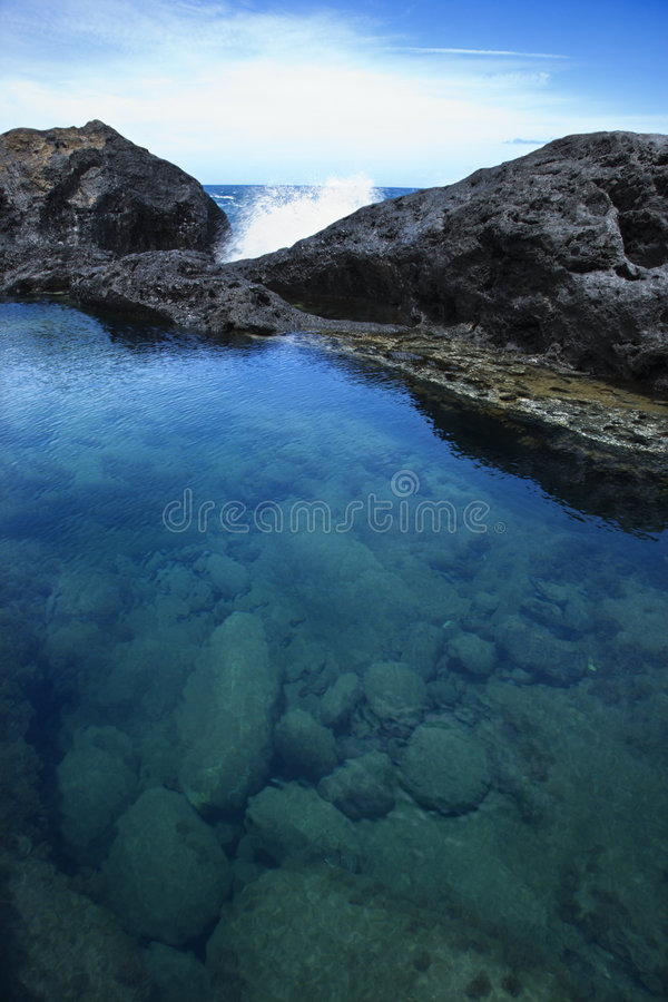Tidal pool in Maui. Tidal pool with wave crashing on rocks in background with blue sky in Maui, Hawaii, USA stock images