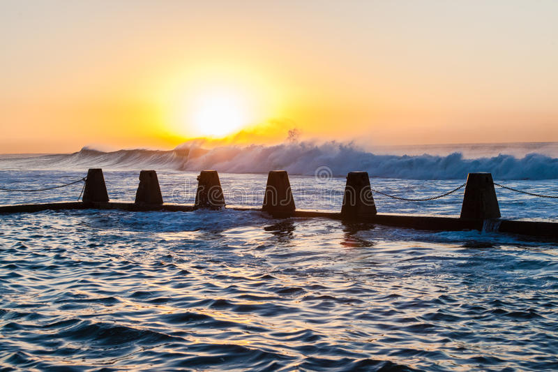 Tidal Pool Ocean Waves Dawn Energy. Ocean waves surging and crashing on high tides with swells breaking large powerful volumes of sea water energy into the stock photography