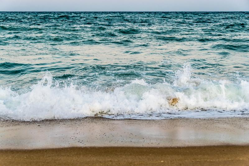 Tidal waves on a sandy beach. Evening walk by the coast of Golden Sands resort in Bulgaria. Last warm days of the hot season 2019 royalty free stock photography