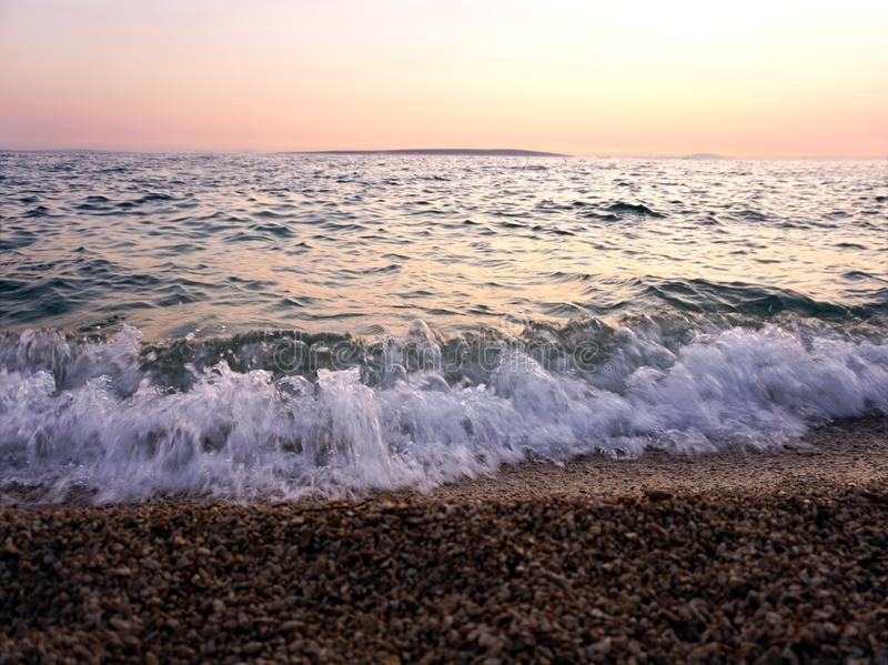 Tidal waves and sea foam on the seashore and pebble beach at sunset royalty free stock photo