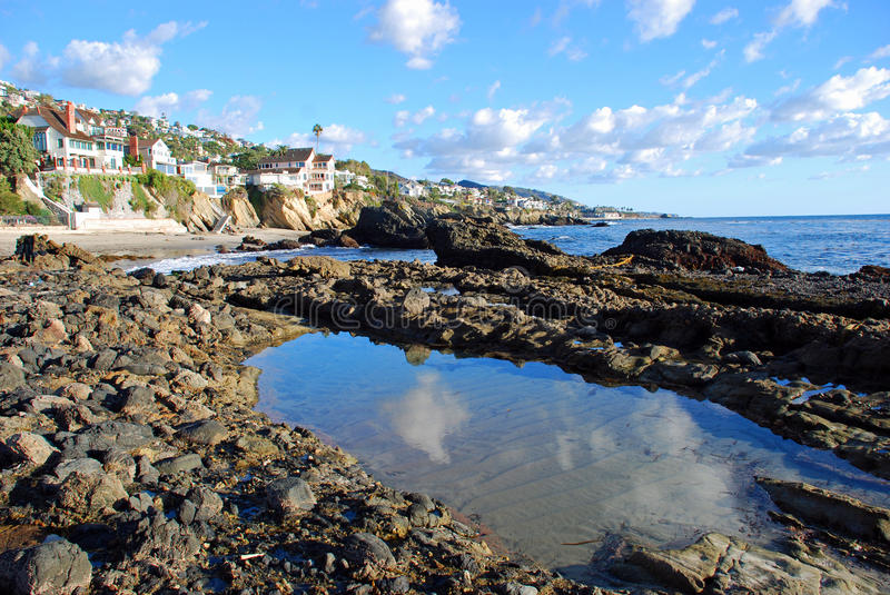 Tide pool and rocky shoreline near Woods Cove, Laguna Beach California. A rocky shoreline and tide pool borders picturesque Woods Cove (upper left)south of royalty free stock photo