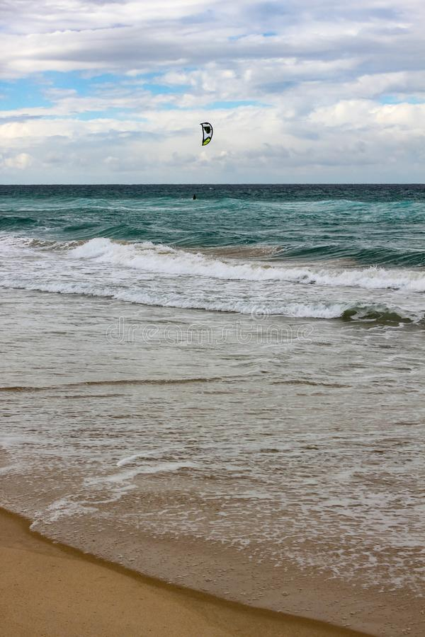 Tide rolling onto the shore with horizon under cloud shadow and kite surfer out in the water - vertical stock image