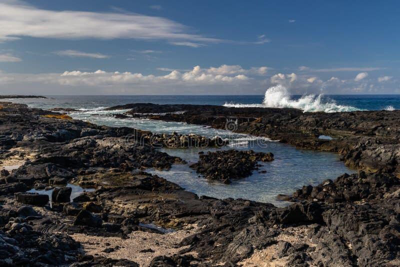 Tidepool sulla spiaggia vulcanica hawaiana Rocce nere in priorità alta; mare, cielo blu e nuvole nel fondo fotografie stock