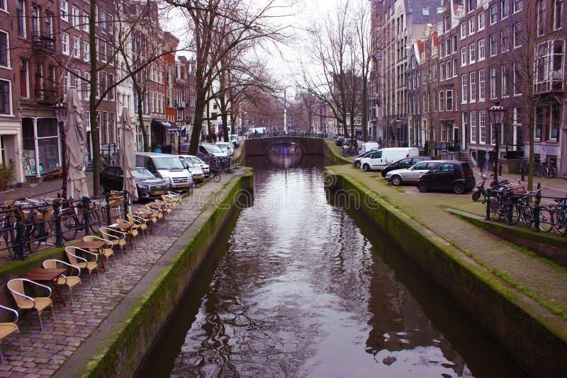 Tidig vårplats i den Amsterdam staden Tours med fartyget på de berömda holländska kanalerna Cityscape med kanalhus i Holland, royaltyfri bild