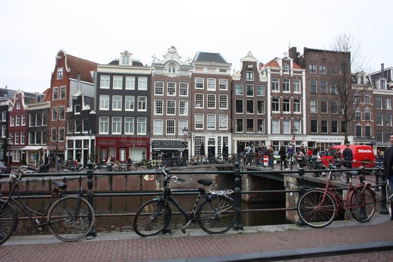 Tidig vårplats i den Amsterdam staden Tours med fartyget på de berömda holländska kanalerna Cityscape med kanalhus i Holland, royaltyfria bilder