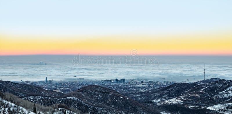Tidig vintermorgon, dimma och smog över staden av Almaty, Kasakhstan arkivfoton