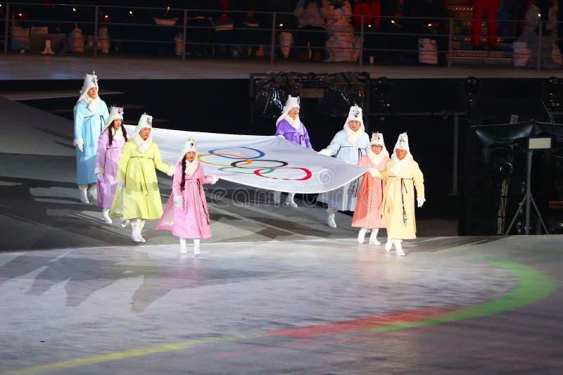 Tidigare sydkoreanska olympier- och olympiskt guldmedaljörer bär den olympiska flaggan in i Olympic Stadium på de 2018 vinterOS:e fotografering för bildbyråer
