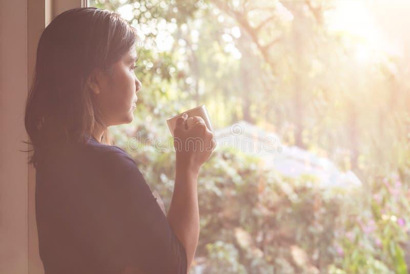 Tidigt funktionsdugligt begrepp: Asiatiskt kvinnaanseende och drickakaffe royaltyfria foton