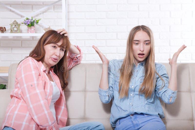 tidigt havandeskap Modern och dottern sitter på hemmastadd bakgrund för soffa Kopieringsutrymme och åtlöje upp royaltyfri bild