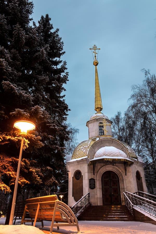 Tidigt på morgonen exponeras ett ortodoxt kapell av en gatalampa som står närliggande royaltyfri foto