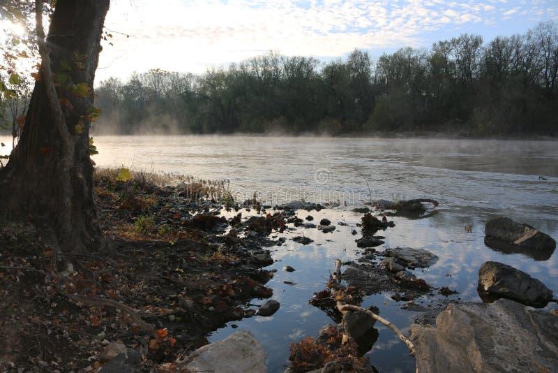 Tidigt på morgonen reflekterar damm från flodbergen arkivfoto