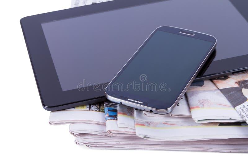 Tidningar, minnestavla och mobiltelefon arkivbild